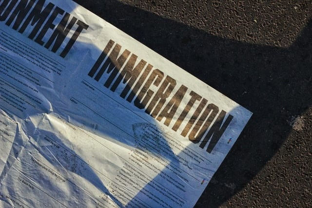 """""""Immigration"""" printed on a white newspaper."""