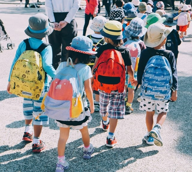 Children walking with colorful backpacks