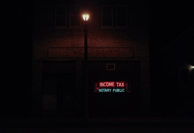 A neon signboard reads 'Income Tax Notary Public' outside a home lit by a street lamp