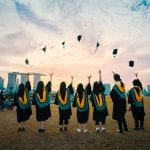 Students throwing up their graduation hats to air
