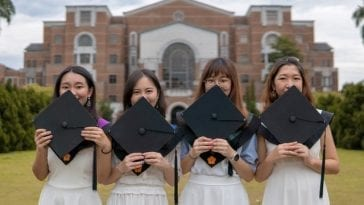 Women college students holding their graduation day caps in front of their college