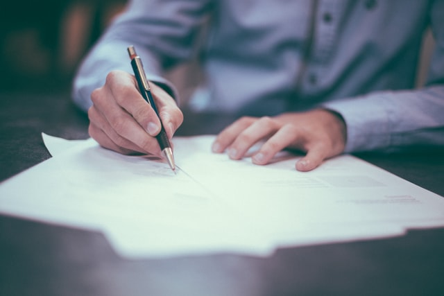 Man writing business letter on paper